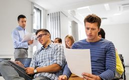 Students with tests and teacher at lecture hall. Education, high school and fail concept - group of students with tests and teacher at lecture hall stock images
