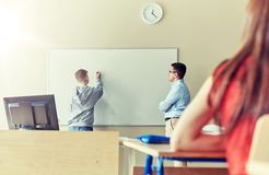 Teacher and student writing on board at school Royalty Free Stock Photos