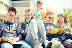 Group of students with notebooks at school yard. Education, high school and people concept - group of happy teenage students with notebooks learning at campus Royalty Free Stock Image