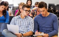 Group of students with papers in lecture hall stock photo