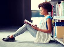 African student girl reading book at library stock images