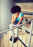 African student girl reading book on stairs stock image