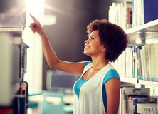 African student girl pointing to book at library stock images