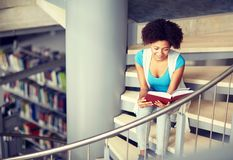 African student girl reading book at library royalty free stock photo