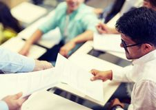 Teacher giving exam test to student man at lecture royalty free stock photography