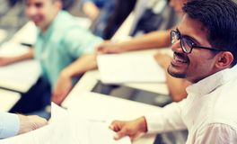 Happy student with exam test or handout at lecture stock images