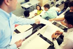 Teacher giving tests to students at lecture hall stock photo