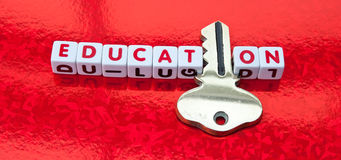 Education holds the key. Text 'education' inscribed in red letters on small white cubes with letter 'i' replaced by a golden key. red background Royalty Free Stock Image