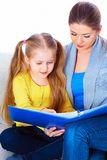 Education at home with parents. Reading book Royalty Free Stock Photo