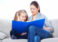 Education at home with parents. Reading book Stock Photos