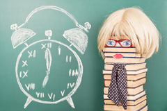 Education idea. Funny education idea, unusual woman teacher in front of blackboard with alarm clock drawing stock photos