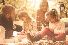 Education is important. Parents in park with their daughters having education and teaching daughters to writing royalty free stock photo