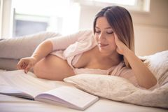 Education is important during pregnancy. Pregnant woman reading book royalty free stock photo