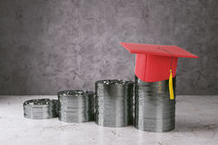 Education and income concept. Abstract silver coins with red graduation cap on concrete background. Education and income concept. 3D Rendering Stock Photo