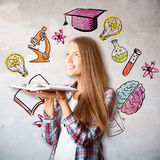 Education and knowledge concept. Side portrait of attractive smiling woman holding open book on concrete wall background with educational sketch. Education and stock photo
