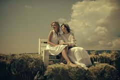 Education and knowledge concept. Two girls reading books on bench on hay Stock Photos