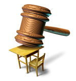 Education Law. And school justice with a judge mallet or judges wooden gavel hammering a student class desk as a metaphor for public safety teacher or student Stock Photo