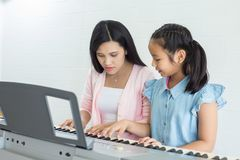 Education music concept. Little girl with teacher learning to play piano indoors Stock Images