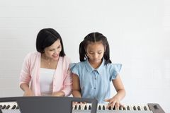 Education music concept. Little girl with teacher learning to play piano indoors Stock Photo