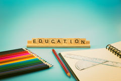 Education notebook and colored pencils royalty free stock photography