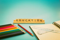 Education notebook and colored pencils stock photography