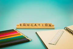 Education notebook and colored pencils royalty free stock photos