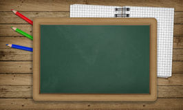 Education, notepad, pencils, blank empty blackboard Royalty Free Stock Photography