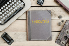 Education on old book cover at office desk with vintage items Royalty Free Stock Photography