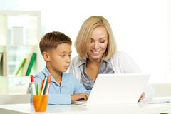Education online. Portrait of pretty tutor and her pupil working with laptop Royalty Free Stock Image