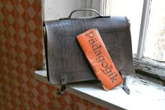 Education over time. An old leather satchel with a pedagogy book by the window Stock Photo