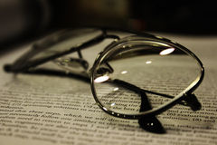 Education. A pair of reading glasses sitting on a book denoting education and work Royalty Free Stock Photo