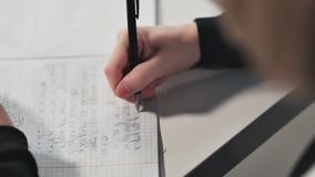 Close-up A schoolgirl writes in a workbook. She`s doing her homework. stock footage