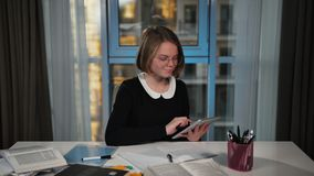 A happy schoolgirl uses a tablet. Does the homework. And writes. stock video