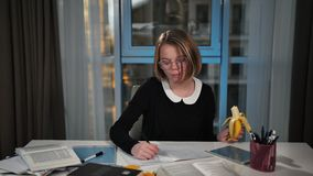 A happy schoolgirl uses a tablet and eats a banana, writes in a notebook for exercises. Lunch break. She`s doing her. Education, people children and learning stock video