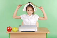 Education, people, children and school concept - young school girl sitting at a desk with a book on her head Royalty Free Stock Images