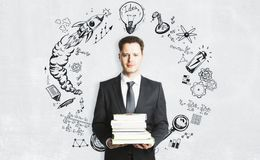 Education and plan concept. Handsome european businessman with books standing on concrete wall background with business sketch. Education and plan concept Royalty Free Stock Photos