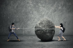 Education problem concept. Education problem with students pulling and pushing heavy stone Stock Photo
