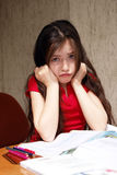 Education problems. Girl hopelessly struggles with homeworks stock photo
