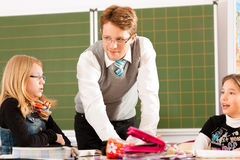 Education - Pupils and teacher learning at school. Education - Pupils and teacher learning at elementary or primary school in the classroom royalty free stock photography