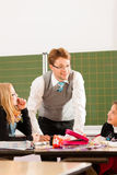 Education - Pupils and teacher learning at school. Education - Pupils and teacher learning at elementary or primary school in the classroom royalty free stock photo