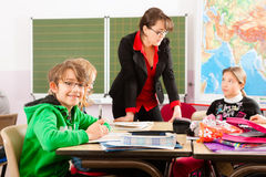 Education - Pupils and teacher learning at school. Education - Pupils and teacher learning at elementary or primary school in the classroom stock photo