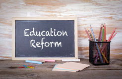Education Reform text on a blackboard. Old wooden table with texture.  Stock Photography