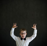 Education rocks boy dressed up as businessman on blackboard background Royalty Free Stock Photography