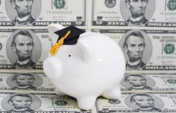 Education savings. Piggy bank with a graduation cap with dollar bill background royalty free stock photos