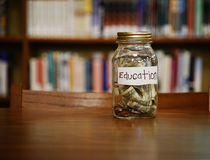 Education Savings Money Jar. A money glass jar filled with dollars and coins with an education label is on a desk in a library with copyspace for a savings or royalty free stock images