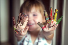 Education, school, art and painitng concept - little girl showing painted hands. Education, school, art and painitng concept - little student girl showing stock images