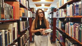 Education and school concept - happy student girl or young woman with book in library stock footage