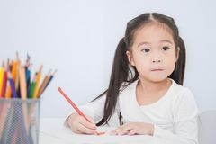 Education and school concept, little asian student girl drawing with pencils at school royalty free stock photography