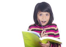 Education and school concept - little girl reading a book and hold pencil Royalty Free Stock Photo