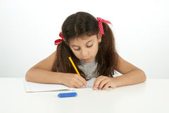 Education and school concept. Little girl writing. With pencil royalty free stock photography